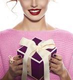 La mujer hermosa con maquillaje de la tarde toma la caja con el presente Imagen de archivo