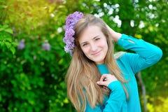 La mujer hermosa con una guirnalda del color de la lila camina en el parque Fotos de archivo