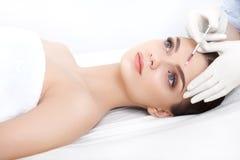 La mujer hermosa consigue inyecciones cosmetología Cara de la belleza Fotografía de archivo