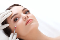 La mujer hermosa consigue inyecciones cosmetología Cara de la belleza Foto de archivo