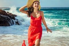 La mujer hermosa corre lejos de ondas en la playa Foto de archivo