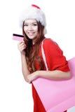 La mujer hermosa de la Navidad feliz toma de la tarjeta de crédito Imágenes de archivo libres de regalías