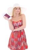 La mujer hermosa del blondie en vestido rojo con el pasaporte y el boleto es Fotos de archivo