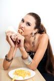 La mujer hermosa del encanto está comiendo los alimentos de preparación rápida Fotos de archivo libres de regalías