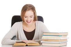 La mujer hermosa del estudiante que se sienta por el escritorio con los libros y aprende Foto de archivo libre de regalías