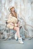 La mujer hermosa del inconformista con el juguete está en la bicicleta Fotografía de archivo libre de regalías
