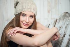 La mujer hermosa del inconformista se está sentando cerca de la pared blanca Fotos de archivo libres de regalías