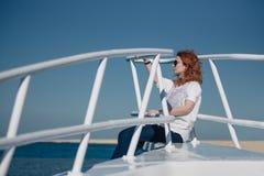 La mujer hermosa del jengibre en vidrios de sol se sienta en un yate blanco en un mar con agua clara de la turquesa Relajación en Fotos de archivo libres de regalías