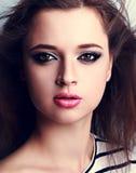 La mujer hermosa del maquillaje con el lápiz labial rosado y los ojos ahumados construyen Foto de archivo