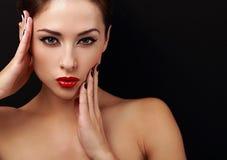 La mujer hermosa del maquillaje con los labios rojos que presentan con las manos acerca a la cara de la piel de la salud Foto de archivo libre de regalías