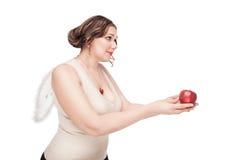 La mujer hermosa del tamaño extra grande como ángel sugiere la manzana Imagen de archivo