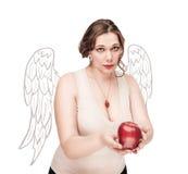 La mujer hermosa del tamaño extra grande como ángel sugiere la manzana Fotos de archivo libres de regalías