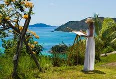 La mujer hermosa, delgada en el vestido blanco pinta el paisaje tropical, mar Imagen de archivo