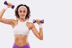 La mujer hermosa deportiva con pesas de gimnasia hace aptitud que ejercita en el fondo blanco para permanecer apta Fotos de archivo