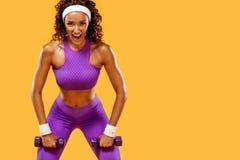 La mujer hermosa deportiva con pesas de gimnasia hace aptitud que ejercita en el fondo blanco para permanecer apta Imagen de archivo libre de regalías