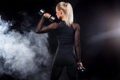 La mujer hermosa deportiva con pesas de gimnasia hace aptitud que ejercita en el fondo negro para permanecer apta Fotos de archivo libres de regalías