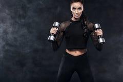 La mujer hermosa deportiva con pesas de gimnasia hace aptitud que ejercita en el fondo negro para permanecer apta Imágenes de archivo libres de regalías