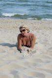 La mujer hermosa en arena en la playa por el mar Imagen de archivo libre de regalías