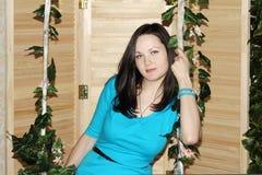 La mujer hermosa en azul se sienta en el oscilación Fotografía de archivo