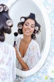 La mujer hermosa en bigudíes de pelo pone maquillaje de la mañana Imagen de archivo
