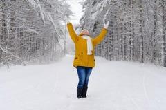 La mujer hermosa en bosque del invierno disfruta en la nieve Foto de archivo