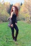 La mujer hermosa en botas se coloca en hierba Imágenes de archivo libres de regalías