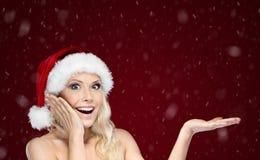 La mujer hermosa en casquillo de la Navidad gesticula la palma para arriba Imagen de archivo libre de regalías