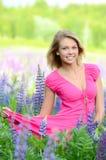 La mujer hermosa en el campo con el altramuz Foto de archivo libre de regalías