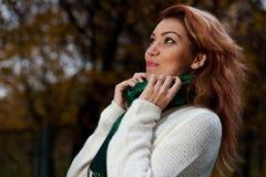 La mujer hermosa en el suéter blanco camina en el parque Fotos de archivo libres de regalías