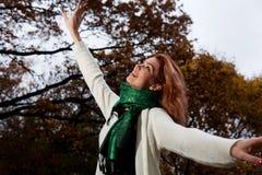 La mujer hermosa en el suéter blanco camina en el parque Imagen de archivo libre de regalías