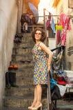 La mujer hermosa en gafas de sol se coloca en el patio de la casa en un cuarto de trabajo imagenes de archivo