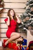 La mujer hermosa en interior de la Navidad celebra feliz en el fondo Foto de archivo libre de regalías