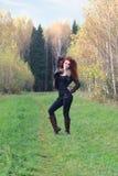 La mujer hermosa en la chaqueta de cuero se coloca en hierba Imágenes de archivo libres de regalías