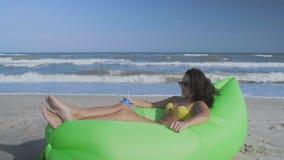 La mujer hermosa en los vidrios de Sun miente en una almohada inflable verde en la playa del mar y bebe un cóctel almacen de video