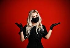 La mujer hermosa en máscara médica negra protectora con las manos separadas abre las palmas gratis manda un SMS al espacio fotografía de archivo