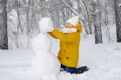 La mujer hermosa en parque del invierno está haciendo un muñeco de nieve Imagen de archivo