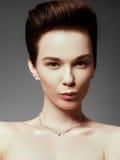 La mujer hermosa en primer pendiente costoso Foto de archivo libre de regalías