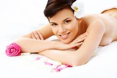 La mujer hermosa en salón del balneario consigue el tratamiento relajante. Imagen de archivo libre de regalías