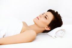 La mujer hermosa en salón del balneario consigue el tratamiento relajante. Fotos de archivo libres de regalías