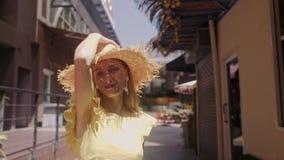 La mujer hermosa en sombrero de paja camina la calle El jugar a la cámara almacen de video