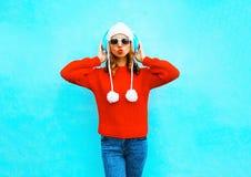 La mujer hermosa en suéter rojo, escucha la música en auriculares inalámbricos Imagen de archivo libre de regalías