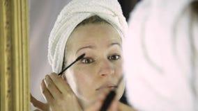 La mujer hermosa en toalla pinta las pestañas delante del espejo almacen de video