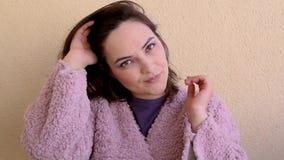 La mujer hermosa en un abrigo de pieles rosado mira la cámara y fija su pelo almacen de video