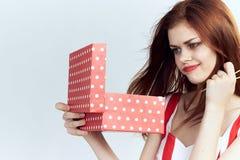 La mujer hermosa en un fondo del blanco sostiene una caja, regalos, retrato, día de fiesta foto de archivo
