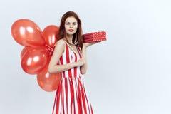 La mujer hermosa en un fondo del blanco sostiene una caja, regalos, retrato, día de fiesta, globos Imagen de archivo libre de regalías