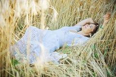 La mujer hermosa en un vestido blanco miente en las espigas de trigo Imágenes de archivo libres de regalías