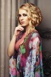 La mujer hermosa en un vestido de colores florales se coloca en el palacio Imagen de archivo