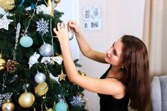 La mujer hermosa en un vestido negro adorna el árbol de navidad Fotografía de archivo