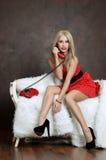 La mujer hermosa en un vestido rojo con el teléfono viejo Foto de archivo