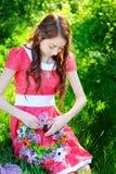 La mujer hermosa en un vestido rojo hace una guirnalda de flores Fotos de archivo